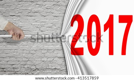 Hand pulling 2017 white curtain covering old brick wall background. - stock photo