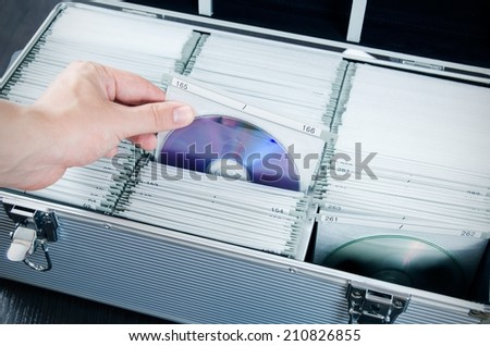 Hand pulls disc from aluminum carrying CD-DVD case - stock photo