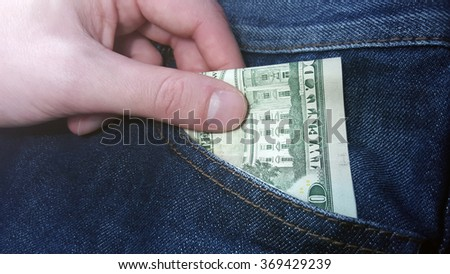 Hand pulls money out of pocket jeans - stock photo