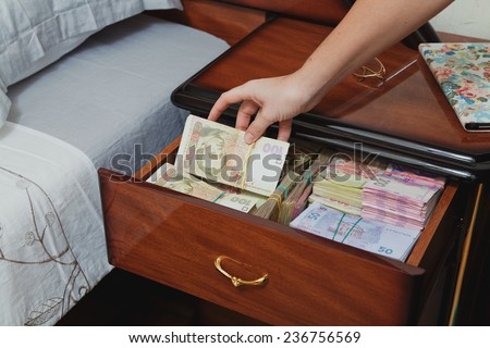 Hand pulls out wad of money from the bedside table filled with Ukrainian cash - stock photo