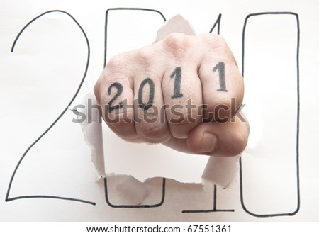 Hand punching through paper on white background - stock photo