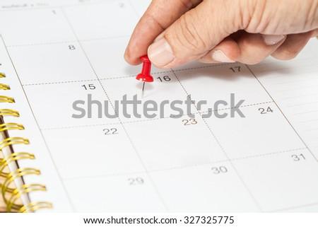 Hand push a pin mark on calendar - stock photo