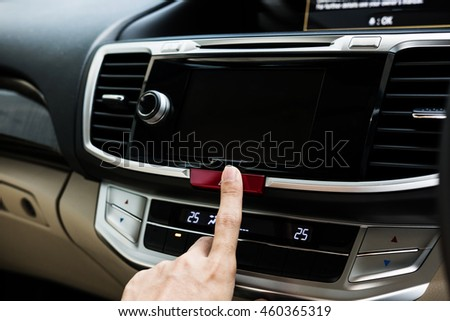 Hand push button in modern luxury car with copy space on monitor screen