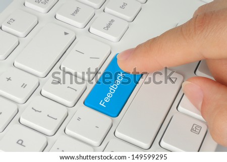 Hand pushes blue feedback button on keyboard close-up