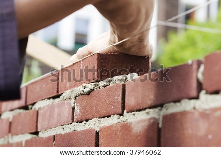 Hand pushes down brick in cement building a wall