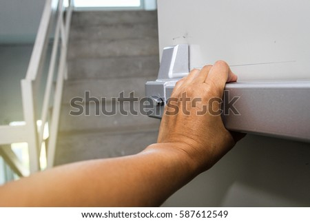 hand pushing a door of fire escape inside the building - safety areas