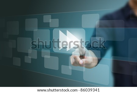 hand pushing a fast forward button on a touch screen interface - stock photo