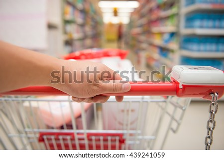 hand pushing a full filled shopping cart - stock photo