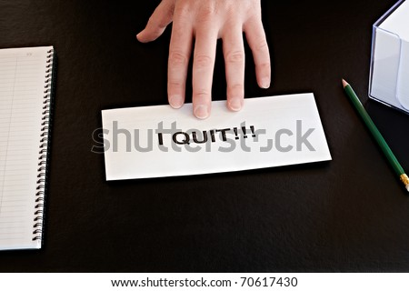 hand pushing a resignation on office desk - stock photo