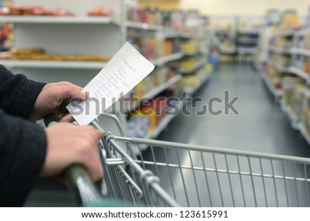 Hand pushing a shopping cart through the aisles of a supermarket, holding a list with groceries, with the daily necessities in handwriting on a slip of paper - stock photo
