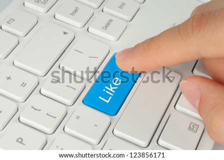 Hand pushing blue like button on keyboard close-up
