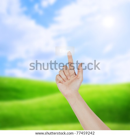 hand pushing enter button on blue sky - stock photo
