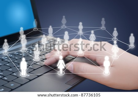 Hand pushing laptop keyboard with social network people. - stock photo