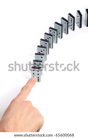 Hand pushing line of domino pieces