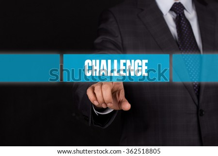 Hand pushing on a touch screen interface-CHALLENGE button - stock photo