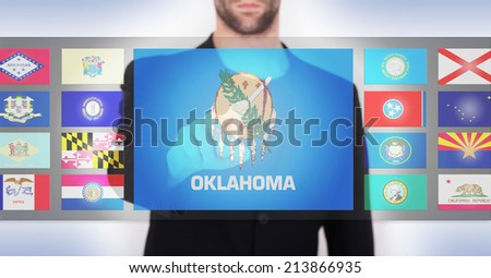 Hand pushing on a touch screen interface, choosing a state, Oklahoma - stock photo