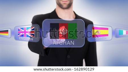 Hand pushing on a touch screen interface, choosing language or country - stock photo