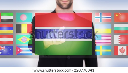 Hand pushing on a touch screen interface, choosing language or country, Gambia - stock photo