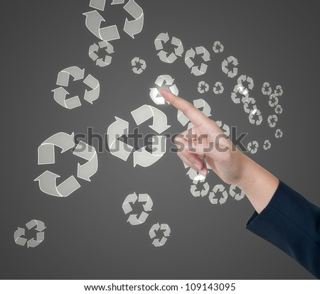 Hand pushing recycle button on a touch screen interface - stock photo