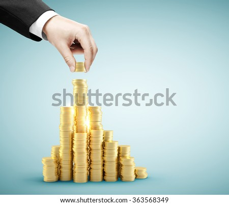Hand put gold coins to money staircase - stock photo