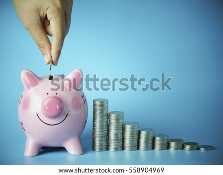 hand put money on pink of piggy bank and pile of coins, concept in save, investment in business