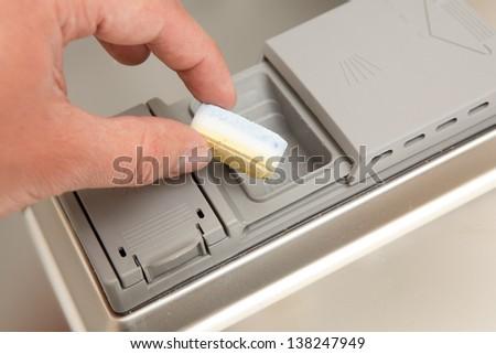 Hand puts tab into dishwasher - stock photo