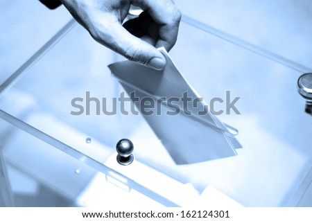 Hand putting a blank ballot inside the box, elections concept, BLUE TONE