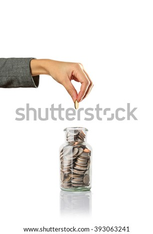 hand putting a coin in jar, saving money - stock photo