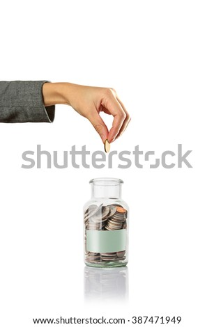 hand putting a coin in jar with blank paper, saving money