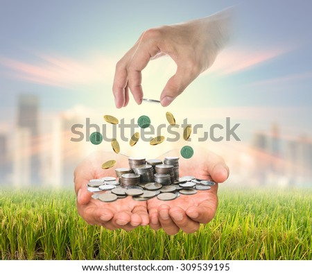 Hand putting a coin in the stack of coins over the hands on rice filed and cityscape blurred background, business investment and saving concept - stock photo