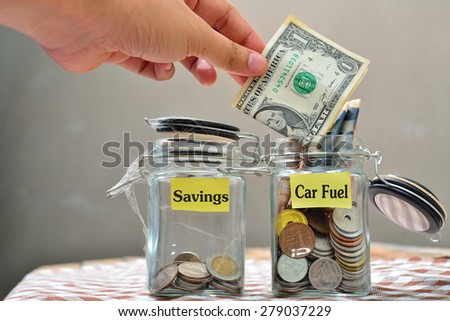 Hand putting a coin into glass jars with 'car fuel' text  - stock photo