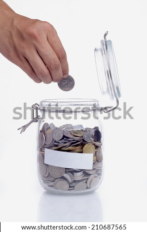 Hand putting a coin into glass jars with empty space for text - stock photo