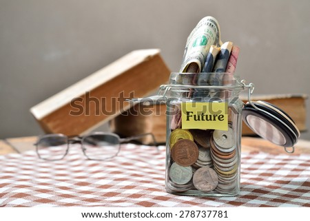 Hand putting a coin into glass jars with 'future' text: Saving for future - stock photo