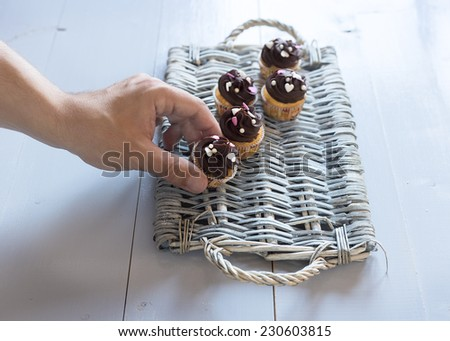Hand putting a delicious chocolate cupcakes on a wicker tray. Sweets on a blue rustic wood table - stock photo