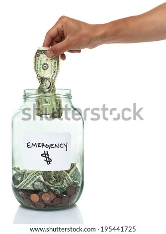 hand putting a dollar bill in an emergency cash savings jar - stock photo