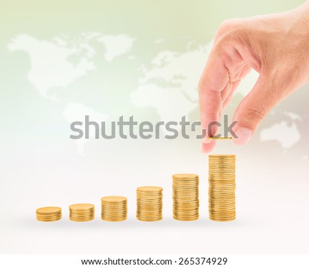Hand putting a gold coin on rising coin stacks with blurred world  map background - stock photo