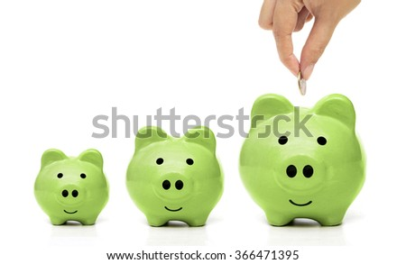 hand putting a golden coin to a green piggy bank - people do green saving - stock photo