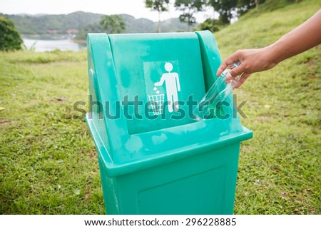 Hand putting a plastic bottle into a recycling bin - stock photo