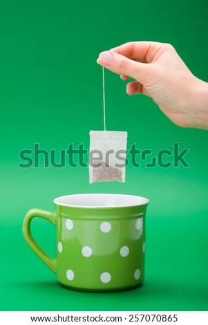 Hand putting a tea bag into green dotted cup - stock photo