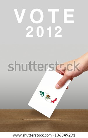 Hand putting a voting ballot in a slot of wooden box on white ba