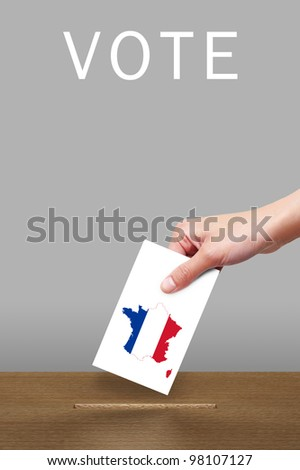 Hand putting a voting ballot to wooden box with flag of France