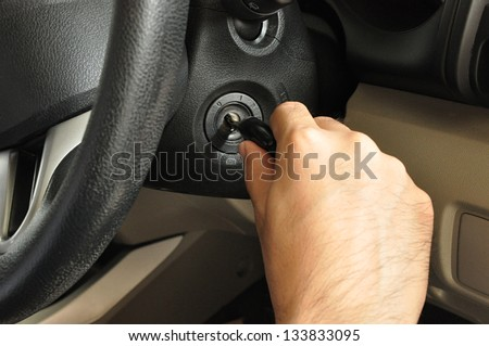 Hand putting car key to the keyhole, starting the car  - stock photo