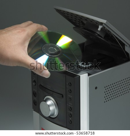 hand putting cd into cd player - stock photo