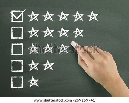 hand putting check mark with chalk on five star rating - stock photo