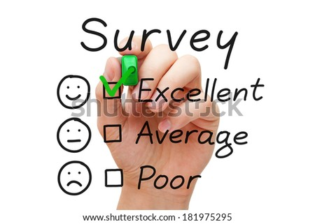 Hand putting check mark with green marker on excellent survey evaluation form. - stock photo