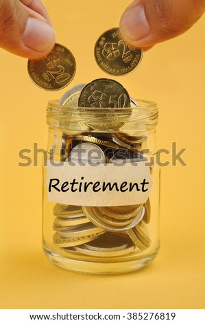 """Hand Putting Coin In Jar with Word """"RETIREMENT"""", Selective Focus - stock photo"""