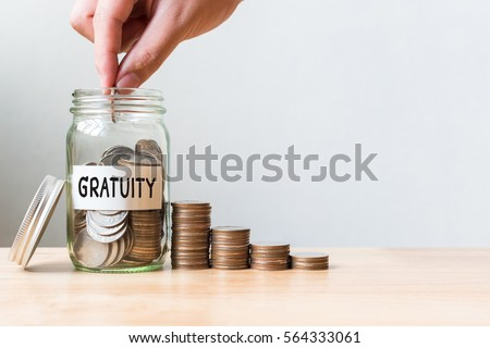 Hand putting coin in jar word gratuity with money stack, Concept business finance and investment