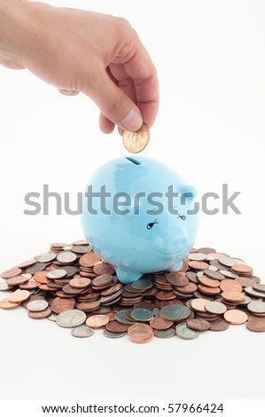 Hand Putting Coin into Piggy Bank that is Already Full - stock photo