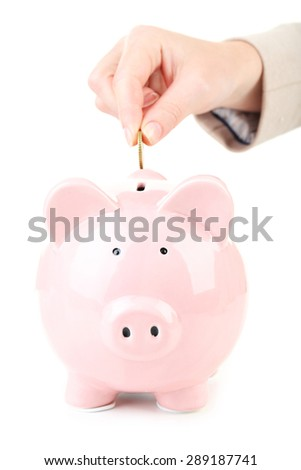 Hand putting coin into pink piggy bank - stock photo