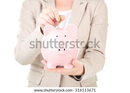 Hand putting coin into pink piggy bank